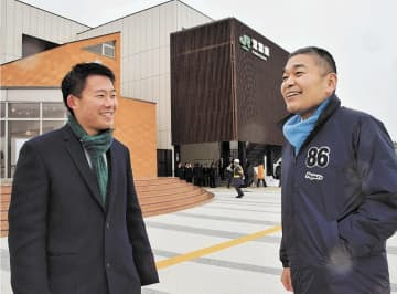 「ダキシメテフタバ」のタオルマフラーを首に巻き、JR双葉駅前に立つ浅野さん(右)と宏介さん=福島県双葉町