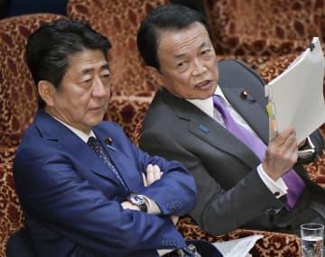 参院予算委で麻生財務相(右)と話す安倍首相=23日午後