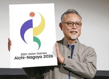 2026年夏季アジア大会のエンブレムが描かれたパネルを掲げる宮下浩さん=23日午後、名古屋市