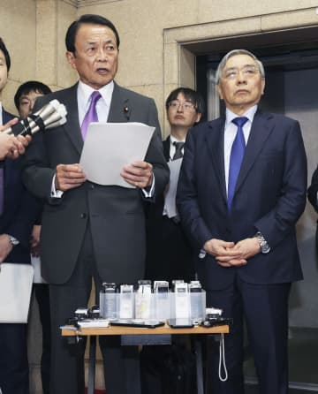 G20財務相・中央銀行総裁の緊急電話会議を終え、報道陣の取材に応じる麻生財務相(左)と日銀の黒田総裁=23日夜、財務省