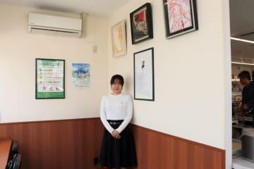 イートインスペースに飾られた平野さん(中央)の作品=大山崎町下植野・ファミリーマート大山崎インター店