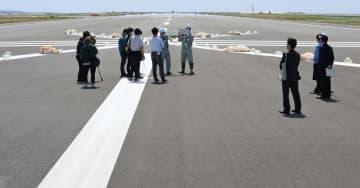 第2滑走路上で、担当者から概要について説明を受ける報道陣=24日午前、那覇空港