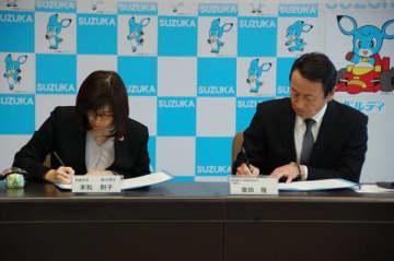 【協定書に署名する末松市長と廣田理事長(右)=鈴鹿市役所で】