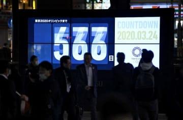 東京五輪開幕までの日数などを伝える大型画面に、重なって表示された数字。新型コロナウイルスの影響で開幕は1年程度延期する方針となった=3月24日夜、東京・新橋駅前