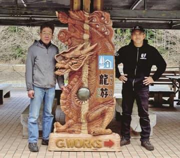 道の駅に設置された龍の看板。右は城所ケイジさん(和歌山県田辺市龍神村福井で)
