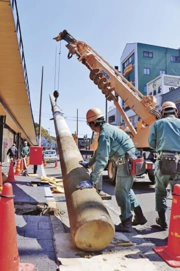 クレーンで引き抜かれた電柱(24日、和歌山県田辺市湊で)