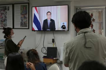 Reporters at Government House on Wednesday watch Prime Minister Prayut Chan-o-cha announcing the enforcement of the emergency decree. (Photo by Chanat Katanyu)