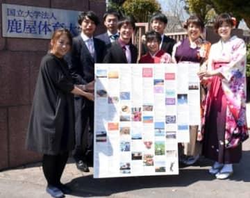 隈崎和代さん(左端)からメッセージが印刷されたパネルを受け取る卒業生=鹿屋市の鹿屋体育大学