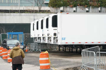 Refrigeration trucks are in place as workers build a makeshift morgue outside of Bellevue Hospital to handle an expected surge in Coronavirus victims on Wednesday, March 25, 2020 in New York. - BRYAN R. SMITH/AFP/Getty Images North America/TNS