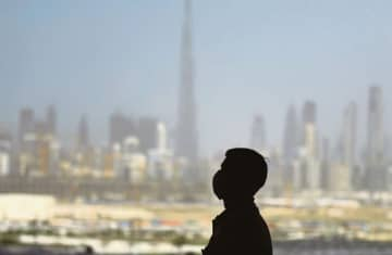 A man wearing a protective mask stands at a racetrack overlooking Dubai following the UAE's decision to postpone the upcoming Dubai Horse Racing amid the COVID-19 coronavirus pandemic.
