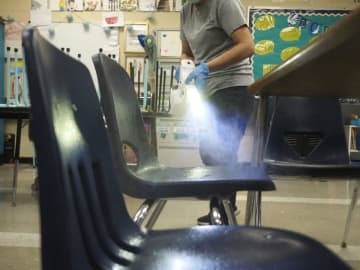 A custodian uses an eltrostatic spray gun to clean a classroom in Highland Park.(Patti Sapone | NJ Advance Media/)