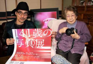 「141歳の写真展」を開く福田サヨさん(右)と孫の東京神父さん=別府市中須賀東町
