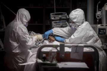 新型コロナ感染患者を治療する医療関係者=ローマ(ゲッティ=共同)