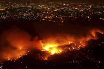 A bushfire ravages Doi Suthep-Pui National Park in Chiang Mai's Hang Dong district on Wednesday night. Local officials and soldiers spent more than 14 hours bringing it under control. Chiang Mai Volunteer Drone Team