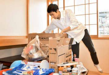 引っ越しの延期を決め、自宅で荷物を確認する郷さん=26日午後、石川町