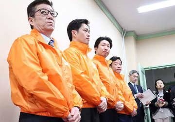 会議後、オレンジジャンパーを着て記者団の取材に応じる大阪市の松井市長、吉村知事、堺市の永藤英機市長ら(左から)=26日、府庁