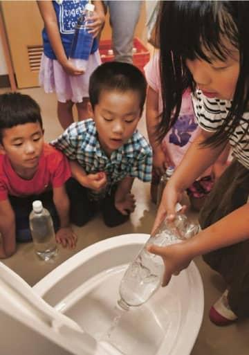 昨年7月にあった防災授業で、災害配慮トイレの使い方を学ぶ児童(和歌山県田辺市芳養町で)