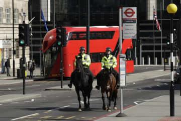 25日、ロンドン市内で馬に乗る警察官ら(AP=共同)