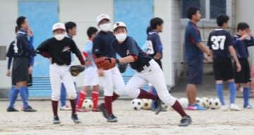 部活動が再開され、軟式野球部員はマスク姿でボールを追い掛けた=27日午前、宮崎市・宮崎西中