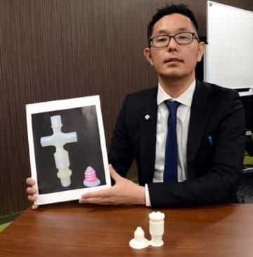 3Dプリンターで作った代用装置の写真を掲げる木阪准教授。手前は実物の一部