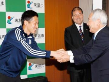 東温市出身者で初のJリーガーとなり、加藤章市長(右)と握手を交わすFC今治のGK岡田慎司=27日、東温市役所