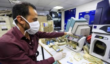 An employee wearing a face mask and gloves counts local currency at a bank in the Yemeni capital Sanaa on March 24, 2020 amid the COVID-19 coronavirus pandemic.