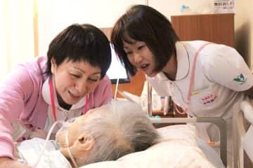 ユマニチュードの技法に基づき、触れながら患者(中央)に話しかける野口課長(左)=佐世保市、佐世保中央病院