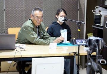 ボランティアの高校生と共に紙飛行機の作り方を解説する藤田教諭(左)
