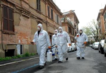 防護服を着て消毒作業に当たる担当者ら=28日、イタリア・ローマ(AP=共同)