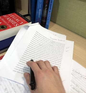 留学先で使ったノートや書籍を並べ、ペンを手にする男性。感染の可能性を考え、帰国後は宿泊施設での生活を続けている=23日(本人提供)