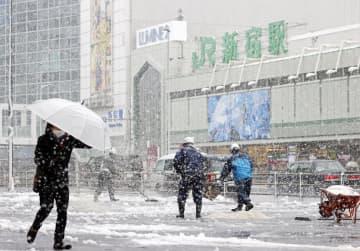 厳しい冷え込みの影響で季節外れの雪が降り、JR新宿駅前では雪かきに追われる関係者の姿も見られた=29日午前