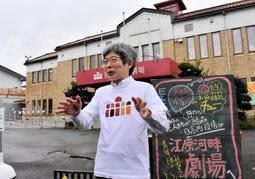 劇場前で思いを語る平田オリザさん。右は地元住民が設置した看板=豊岡市日高町日置