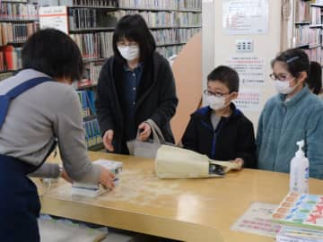 花巻図書館で多くの図書を借り受ける利用者