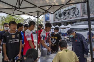 バンコクのムエタイ競技場の外につくられた簡易検査施設に並ぶムエタイ選手ら=19日(AP=共同)