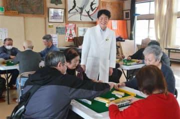 健康マージャンを楽しむ同好会員を見守る大田教授(中央)