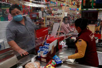メキシコ首都近郊トルーカのスーパーマーケットで、新型コロナウイルス感染拡大防止のためプラスチックシートを張って接客するレジ係=28日(ロイター=共同)