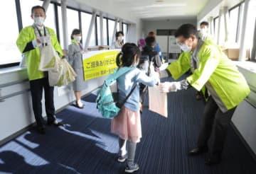 宮崎―名古屋線就航の記念品を配布するソラシドエアの社員=29日午前、宮崎市・宮崎ブーゲンビリア空港