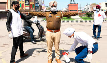 A volunteer sprays disinfectant on a policeman at a street during a government-imposed nationwide lockdown in Amritsar on Saturday.