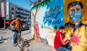 A Palestinian artist paints a mural in the southern Gaza Strip, reading 'by fighting the epidemic, we protect the human being and preserve the earth.'