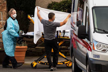 Health care workers transport a patient on a stretcher into an ambulance at Life Care Center of Kirkland on Feb. 29, 2020 in Kirkland, Wash. - David Ryder/Getty Images North America/TNS