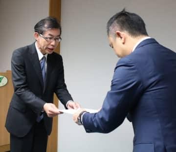 【鈴木知事(右)に報告書を手渡す村瀬委員長=三重県庁で】