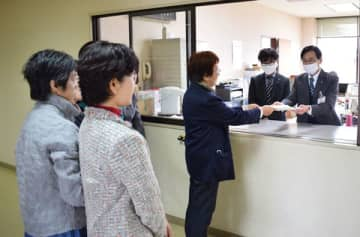 町田忠夫市議会事務局長(右端)に抗議文を手渡す嵐山町の渋谷登美子町議(右から3人目)=30日午前、日高市役所