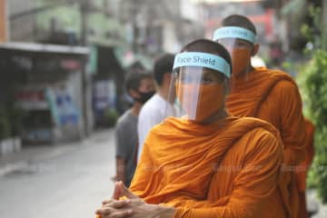 Monks of Wat Matchantikaram in Bang Sue district wear face shields during their alms-taking procession on Tuesday. (Photo by Nutthawat Wicheanbut)
