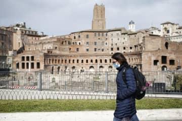 ローマ中心部の「トラヤヌス帝の市場」跡の前を、マスク姿で歩く女性=3月31日(AP=共同)