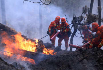 Armed police forces work to put out a blaze at Lushan Mountain in Liangshan Yi autonomous prefecture in Southwest China's Sichuan province, on March 31, 2020. [Photo by Li Jieyi/for chinadaily.com.cn]