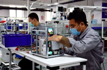 Employees work on the production line of a ventilator manufacturing factory in Sanhe, Hebei province. [Photo/Xinhua]