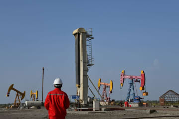 Workers are seen near pumpjacks at a China National Petroleum Corp (CNPC) oil field in Bayingol, Xinjiang Uighur Autonomous Region, China, August 7, 2019. [Photo/Agencies]