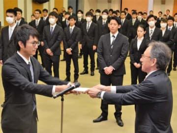 玉城デニー知事(手前右)から辞令を受け取る新規採用職員たち=1日、県庁