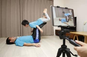 子どもと自宅でできる「親子体操」の動画を作成している「コーディスポーツ」の寺尾大地さん(下)=東京都江戸川区