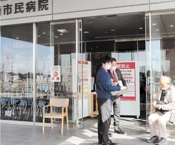 病院を訪れた患者(右)に入館禁止を告げる職員=31日午前8時45分ごろ、宮城県大崎市の大崎市民病院